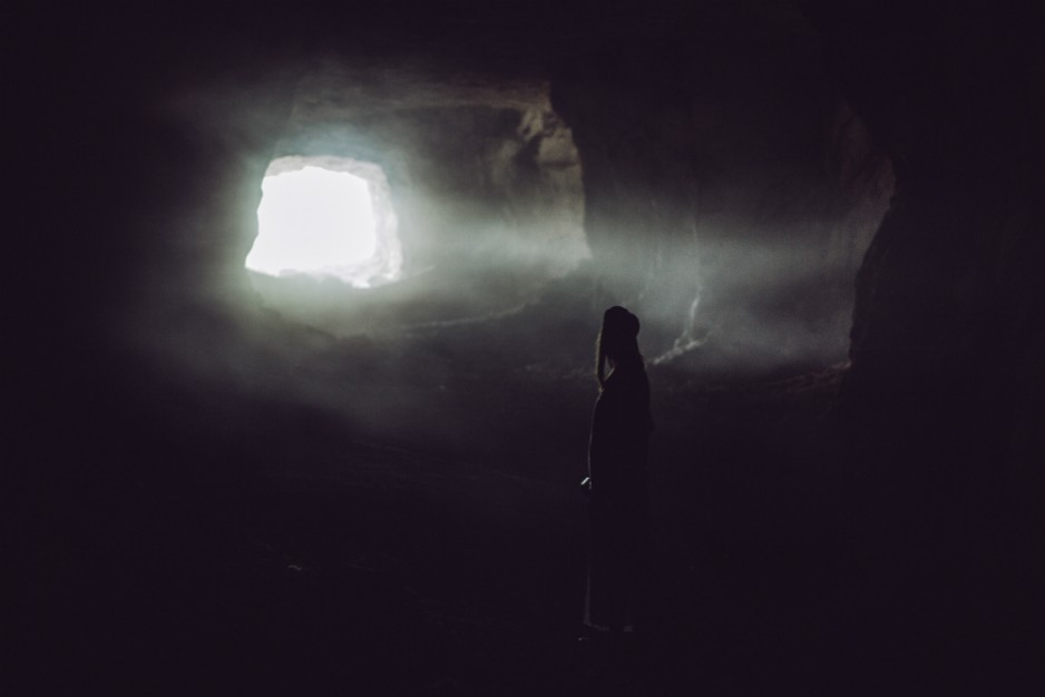 A photo of a woman in a cave looking toward the light coming from the opening.